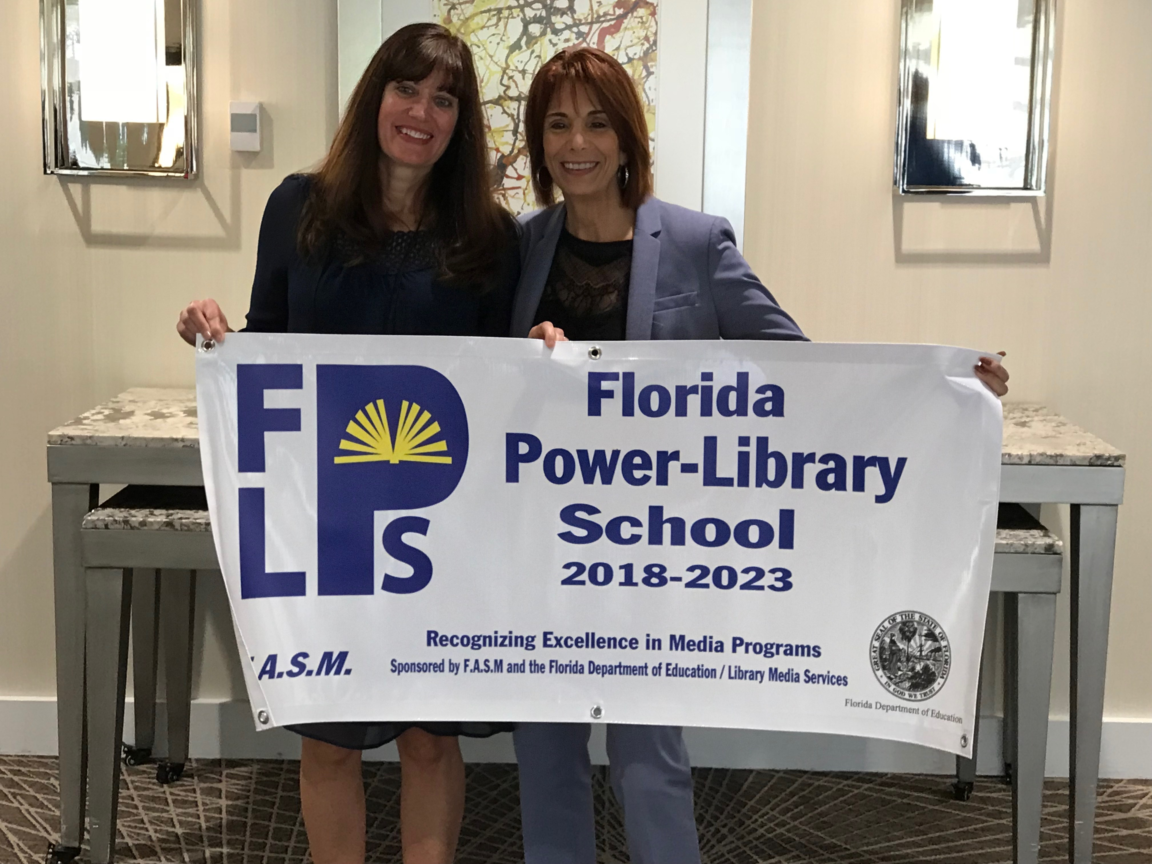 Principal, Cathy Corsaletti and Media Specialists, Tara Cain, with Florida Power-Library School banner